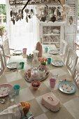 Mit Anhängern dekorierte Pendelleuchte über Tisch mit aufgemaltem Schachbrettmuster, pastellfarbenes Geschirr im Shabby Look
