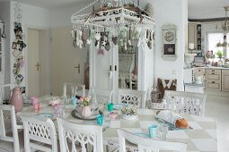 Chandelier decorated with pendants above table with painted chequered top and collection of white-painted wooden chairs
