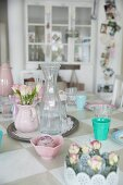 Posy of roses, pastel vintage-style crockery and glass carafe on table with painted chequered top