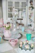 Rosensträusschen, pastellfarbenes Nostalgie Geschirr und Glaskaraffe auf Tisch mit Schachbrettmuster