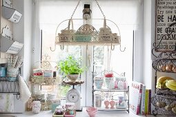 Suspended basket with hooks and floral crockery on small vintage metal shelves in front of kitchen window