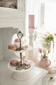 Dried roses on antique china cake stand on white-painted kitchen dresser