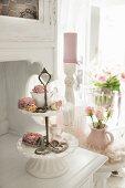 Antike Porzellanetagere mit getrockneten Rosenblüten auf weiss lackiertem Küchenbuffet