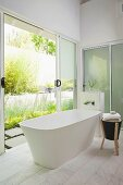 Free-standing bathtub in modern bathroom with open sliding door leading to terrace