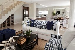 White, open-plan interior with wooden installations, blue and white geometric scatter cushions and deep blue ottomans