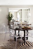 Ghost chairs and round Colonial-style table on zebra-patterned rug