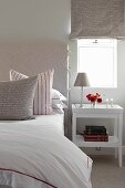 Bedside table below window with Roman blind and scatter cushions on bed in white bedroom