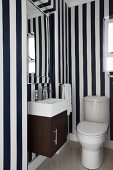 Toilet with compact washstand, bevelled mirror and blue and white striped wallpaper
