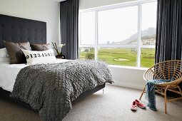 Double bed in bedroom with view of landscape through panoramic window
