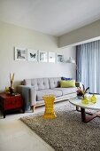 Grey couch and round table on long-pile rug in living room