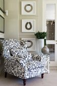 Black and white floral armchair in front of framed necklaces