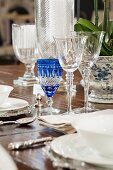 Detail of table set with crystal glasses, white crockery and silver cutlery
