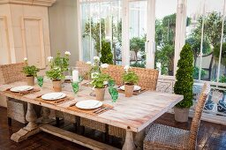 Set wooden table, wicker chairs, green crystal glasses and geraniums