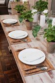 Table set with green crystal glasses, woven place mats and geraniums in terracotta pots