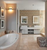 Elegant bathroom with large stone tiles, oval bathtub and twin washstand