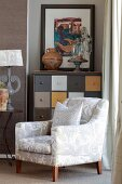 White, lustrous armchair in front of chest of drawers with multicoloured drawers in niche