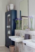Mirror and vases of iris on sill above sink next to blue-painted, glass-fronted towel cabinet