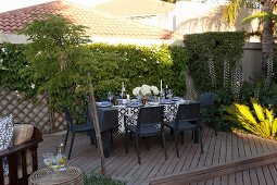 Festively set table and climber-covered wall on courtyard terrace