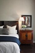 Bed with velvet headboard an antique Oriental bedside cabinet