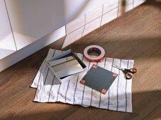 Spiegelfliesen um den Sockel unter den Küchenfronten anbringen