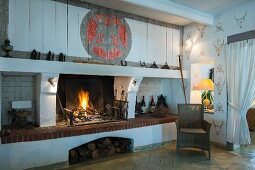 Dark wicker chair in corner next to fire in open fireplace and table lamp in aperture in wall