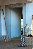 Floor lantern and wicker trunk on wooden terrace next to open door