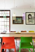 Retro pendant lamps above table with live-edge wooden top, plastic chairs in foreground and modern art in background