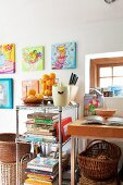 Cookery books and retro citrus press on metal shelves below colourful acrylic paintings on wall