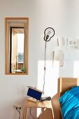 Modern wooden bedside table, sconce lamp and mirror next to bed