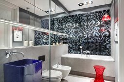 Designer bathroom in shades of grey with red accents