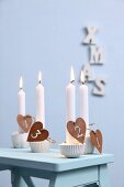 Advent candle holders made from silicone muffin cases, plaster and numbers on heart-shaped pendants
