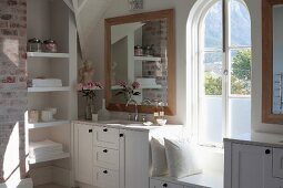 Elegant, rustic bathroom; custom washstand with white base cabinets, fitted shelving in niche, arched window and window seat