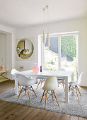 Classic chairs around white table below modern pendant lamps in front of French windows