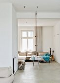 Modern interior with comfortable corner sofa below window and climbing rope hanging from ceiling