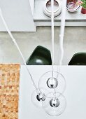 Top view of pendant lamps with spherical glass lampshades above dining table