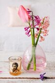 Hyacinths and tulips in pink glass vase next to tealight holder printed with retro-style photo on wooden surface