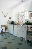 Modern kitchen counter below window and antlers hung on wall of rustic kitchen; tiled floor with dark accent tiles