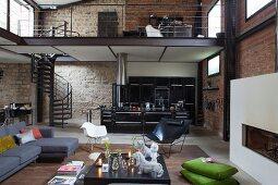Loungebreich und offene Küche in Loftwohnung mit Ziegel- und Natursteinwänden, Blick auf Galerie