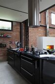 Black kitchen counter below cylindrical stainless steel extractor hood in front of brick wall