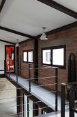 Gallery with stainless steel and steel rope balustrade in loft apartment