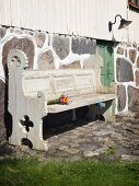 Carved, rustic-style, weathered wooden bench against stone wall base of country house