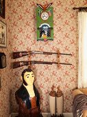 Painted figurine in corner below hunting rifles on wall with floral wallpaper
