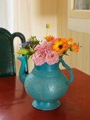 Bouquet in blue-grey teapot; rustic ambiance