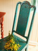 Bunch of mimosa on metal chair with peeling paint in rustic interior
