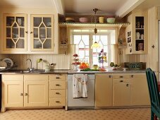 Kitchen counter with cream wooden fronts below window in rustic kitchen