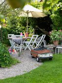 Retro-style pedal car on gravel path and idyllic seating area with table and chairs below parasol in garden