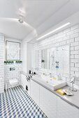 Modern, white bathroom with tiled walls & floor, long washstand with base cabinets & strip light over mirror; modern artwork above wall-mounted toilet in background