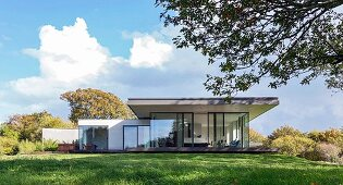 Classic modern house with projecting roof and glass facade on hill in open, summery landscape
