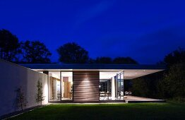 Classic modern house at night with illuminated interior