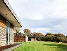 Classic modern house with wood and glass facade and projecting roof in summery landscaped garden